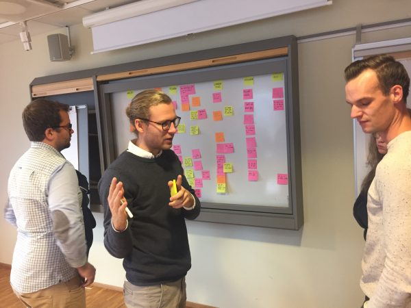 Three participants brainstorming with post-it notes
