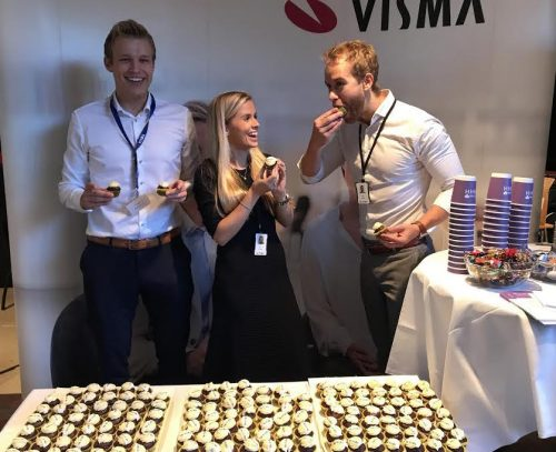 Management trainees on Visma stand holding cupcakes