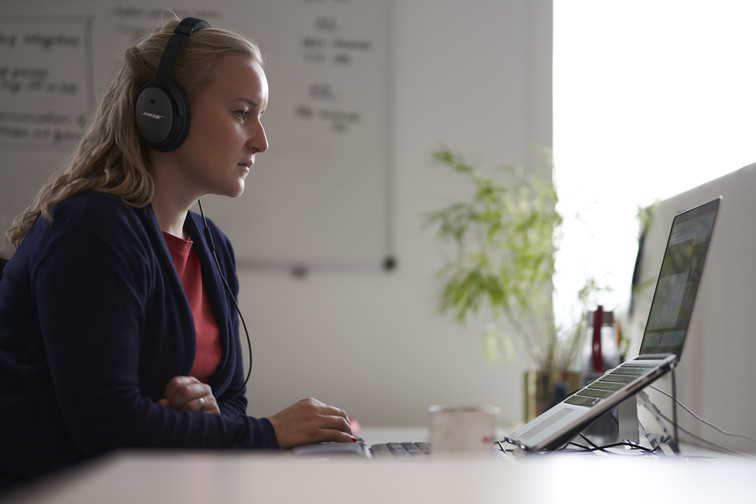 Woman working on computer with headset on