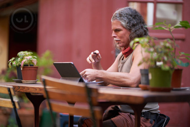 Man in a brown singlet sitting on a table outside looking at his laptop