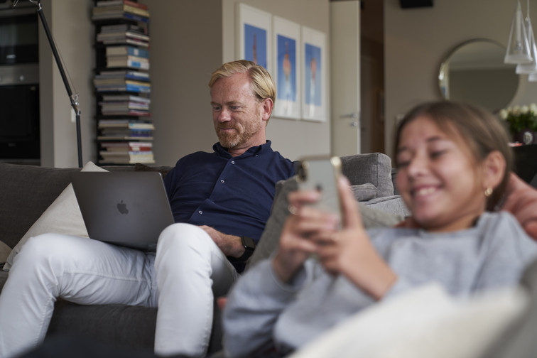 Man and girl sitting in a sofa looking at a laptop and mobile phone