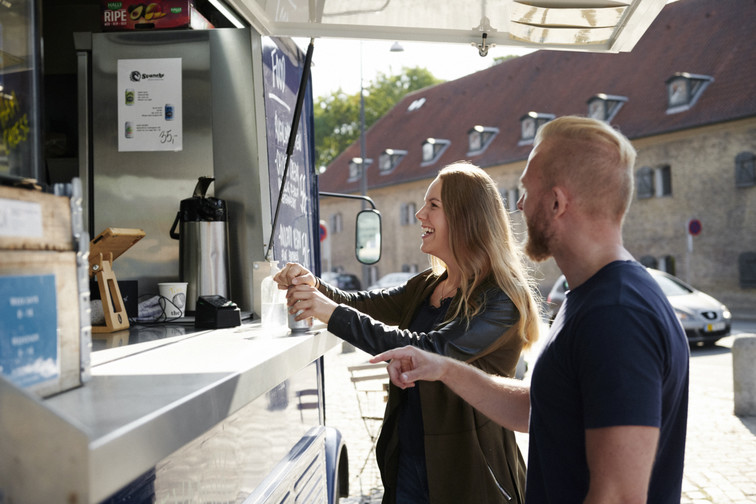 man and woman buying coffee from a coffee truck