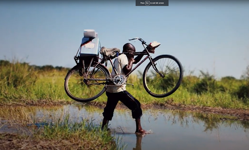 A man carries his bike with a cooler containing the Covid vaccine across a river.