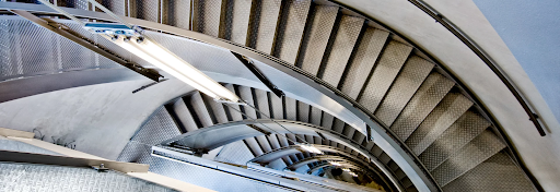 A spiral staircase leads down many floors in a classic building.